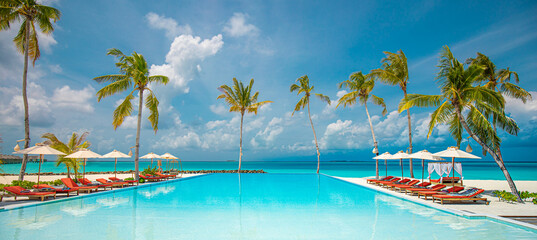 Fototapeta Relax tourism landscape. Luxurious beach resort with swimming pool and beach chairs or loungers leisure lifestyle, under umbrellas, palm trees, blue sky. Summer travel and vacation background concept obraz