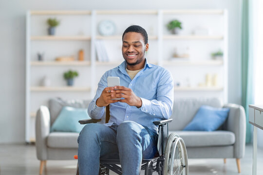 Disabled black man in wheelchair using smartphone, browsing web or watching movie at home