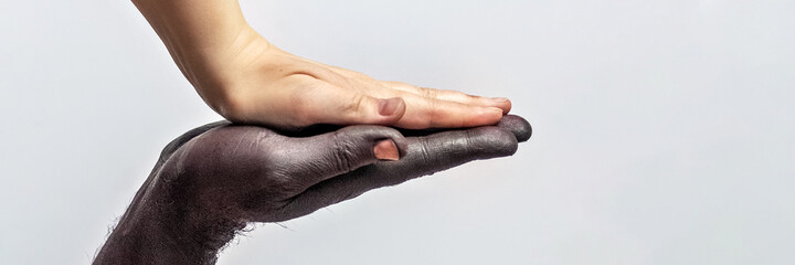 Black male and white female hands, open palms to each other. A symbol of the struggle for black rights in America. The concept of equality and the fight against racism.Banner. Wall mural