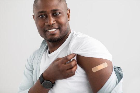 Virus protection. Happy black man holding up shirt sleeve showing the bandage after corona vaccine shot