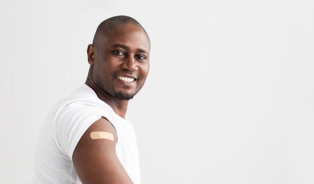 Covid-19 vaccination. Smiling african american man showing his arm with an adhesive bandage, copy space