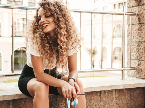 Young beautiful sexy smiling hipster woman with afro curls hairstyle.Trendy female in summer clothes.Positive female with blue penny skateboard posing on the street background