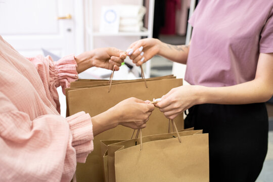 Close-up of customer taking paper shopping bags from the saleswoman in the shop