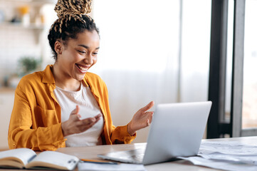 Obraz Online communication. Confident joyful beautiful african american young female student or freelancer with afro dreadlocks, study remotely, talks by online conference with coworkers or teacher, smile - fototapety do salonu