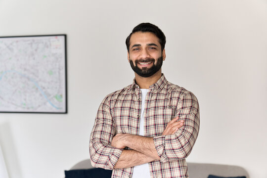 Portrait of young happy indian business man looking at camera standing with arms crossed at home office. Eastern confident male professional, smiling student, ethnic bearded entrepreneur, headshot.