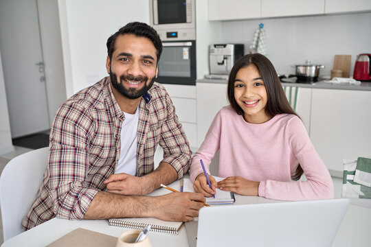 Happy young indian parent father helping teenage child daughter distance learning online together at home. Teen school kid girl studying in kitchen with dad looking at camera sitting at kitchen table.