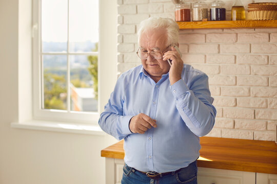 White-haired senior man making phone call and ordering food or meal delivery standing in the kitchen. Mature grandfather staying home and keeping in touch with family talking with them on mobile