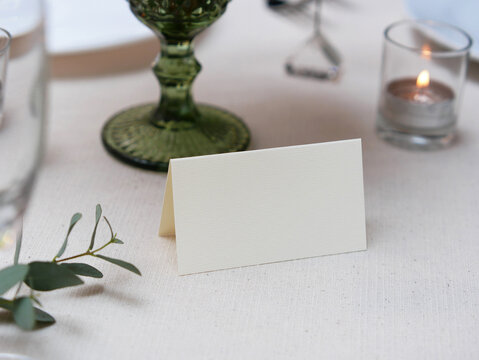 Mockup white blank space card, for Name place, Folded, greeting, invitation on wedding table setting background. with clipping path