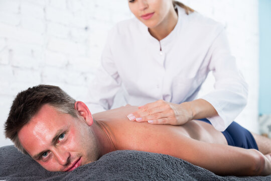 Portrait of young man enjoying relaxing massage by professional masseuse