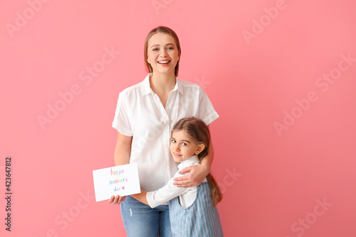Little girl and her mom with greeting card for Mother's Day against color background