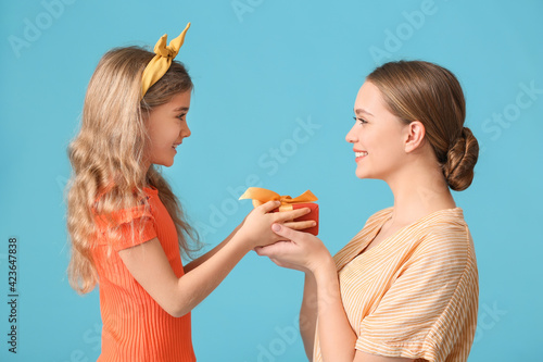 Little girl greeting her mom on Mother's Day against color background