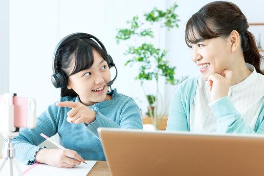 リモート授業を受ける女の子とパソコンをする母親