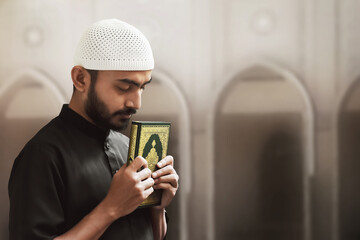 Religious asian muslim man holding holy quran
