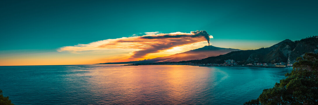 Panoramic view of Mount Etna at sunset by the sea. Last eruption of Mt Etna