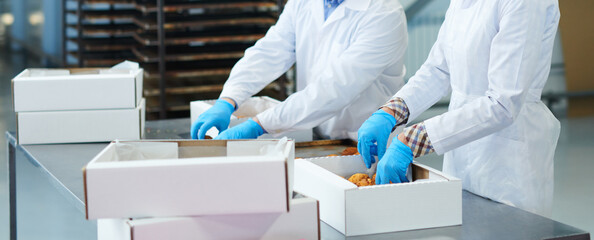 Confectionery factory employees packing pastry into boxes