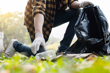 Obraz Man's hands pick up plastic bottles, put garbage in black garbage bags to clean up at parks, avoid pollution, be friendly to the environment and ecosystem - fototapety do salonu