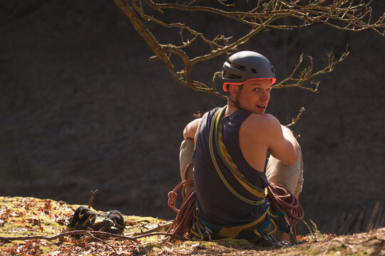 climber sitting at the cliff edge after successfully making it to the top wearing helmet, rope and having other climbing gears around him to be safe