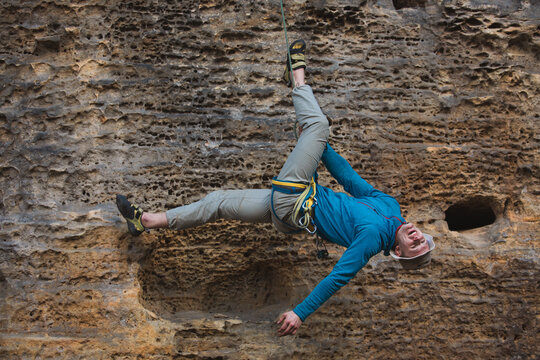 male climber making acrobatics tricks hanging down on a rope from a cliff laying back laughing and having a good time