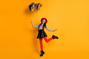 Full length body size view of lovely trendy cheerful girl holding heart air balls dancing having fun isolated on bright yellow color background