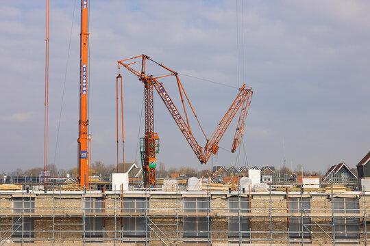 Mobile tower cranes raising at Dutch construction site apartment building