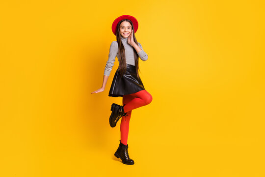 Photo of little shy lady hand cheek wear striped turtleneck hat leather skirt footwear isolated yellow color background