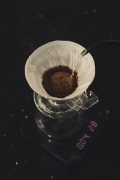 pouring a hot water over V60 coffee in filter to make a steaming pot of coffee