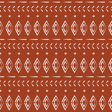 Modern boho tribal mud cloth print with diamond shapes. Decorative abstract art. Seamless pattern vector. White motifs on rust sienna brown background. Repeatable. Wrapping, wallpaper, fabric design.