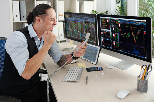 Emotional angry trader screaming in telephone receiver after loosing money in stock market
