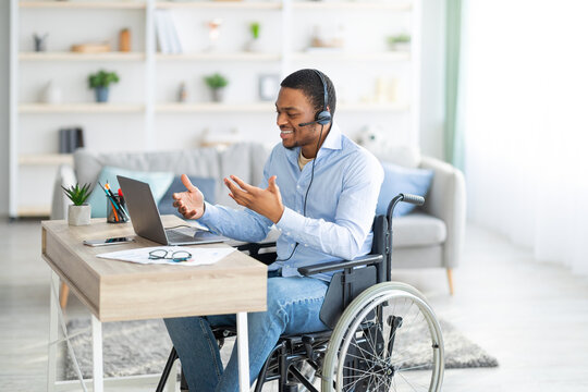 Disabled black guy with headset communicating online on laptop, having business meeting from home