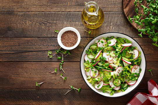Radish and cucumber salad with fresh green onion in bowl