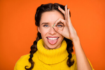 Portrait of brown hair optimistic girl show ok sign tongue out wear yellow sweater isolated on...