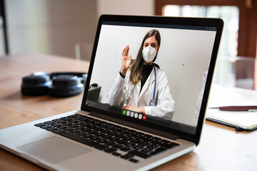 Video call of female doctor wearing face mask with her patient at home in quarantine during a...
