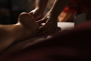 Professional masseuse doing foot massage with oil in spa