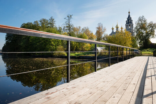 View of the Trinity Church in the village of Drachevo, Moscow region and the bridge over the water channel on a sunny autumn day