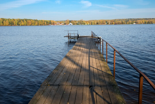 View of the wooden boat pier on the reservoir in an autumn day