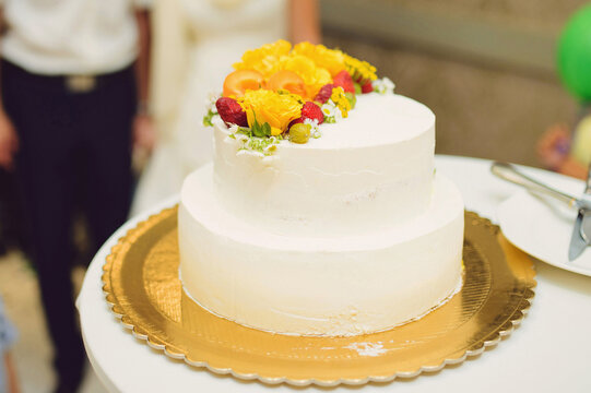 white cake with fruits and flowers