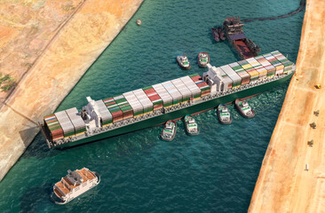 Wall Murals Ever given has been freed in Suez Canal. Effort to refloat vast wedged container cargo ship by tug boats, dredger ship 3D illustration. Giant cargo ship dislodged and refloated in Egyptian Suez canal