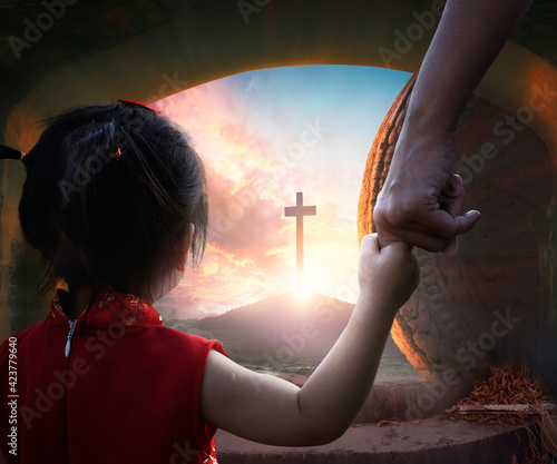 Easter concept: Child's hand holding mother's finger on blurred The cross of jesus christ background.