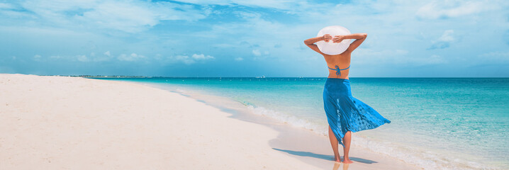 Beach vacation happy woman walking on summer travel Caribbean holiday with arms behind head wearing sun hat and sarong skirt. Ocean panoramic banner background. Elegant lady tourist.
