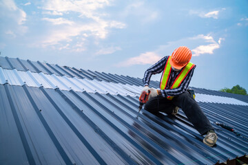 Obraz Asian Roofer worker safety wear using air or pneumatic nail gun and installing on new roof metal sheet, Roof concept of residential building under construction. - fototapety do salonu