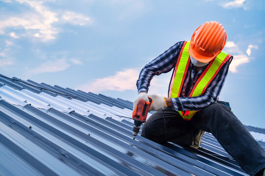 Close up Roofer worker safety wear using air or pneumatic nail gun and installing on new roof metal sheet, Roof concept of residential building under construction.