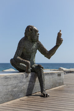 """BADALONA, SPAIN-MARCH 29, 2021: Monkey statue on the seafront of Badalona by Susana Ruiz Blanch. The monkey has the face of Charles Darwin, and she holds a bottle of """"Anis del Mono""""."""