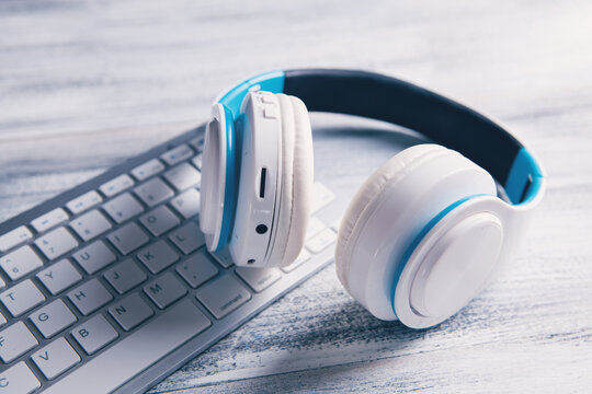 white headphones with computer listening to audio book or music