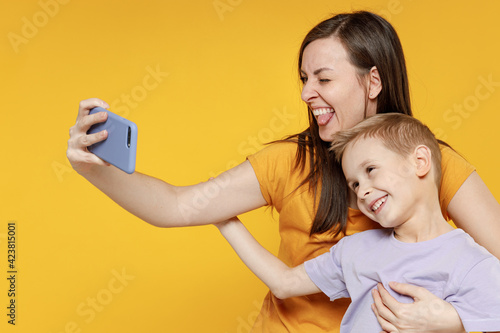 Happy young woman have fun child baby boy 5-6-7 years old in violet t-shirt do selfie shot on mobile phone. Mommy little kid son together isolated on yellow background studio Mother's Day love family