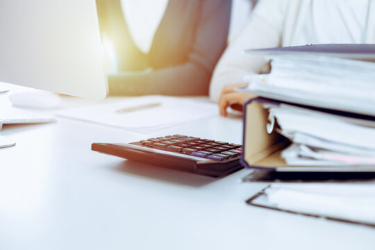 Accountant checking financial statement or counting by calculator income for tax form, hands closeup. Business woman sitting and working with colleague at the desk in office. Tax and Audit concept