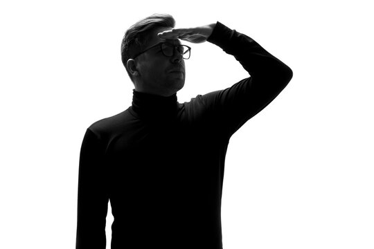 Silhouette of man peering ahead into the distance, with hand on his forehead
