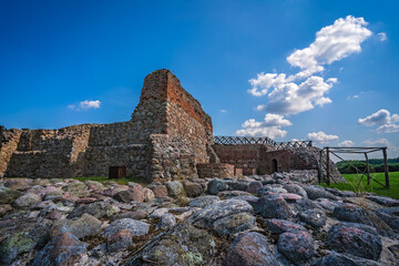 Fototapeta Ruins of Wenecja castle in a field under the sunlight and a blue sky in Poland obraz
