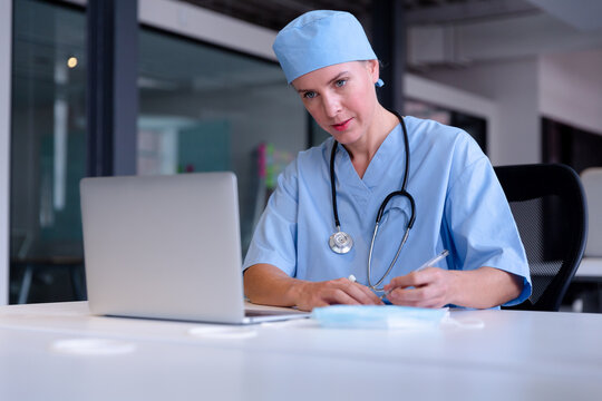 Caucasian female doctor at desk using laptop taking notes during video call consultation