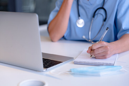 Midsection of caucasian female doctor using laptop taking notes during video call consultation