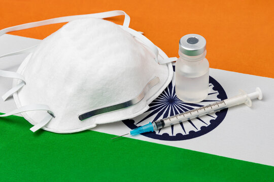 India flag, n95 face mask, needle syringe and vial. Concept of Covid-19 coronavirus vaccine distribution, supply shortage and healthcare crisis